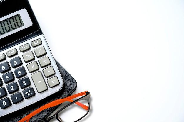 Calcolatrice con libro e bicchieri sul tavolo bianco, copia spazio per testo o display del prodotto