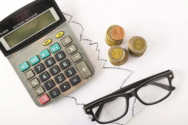 Calcolatrice con monete sul tavolo