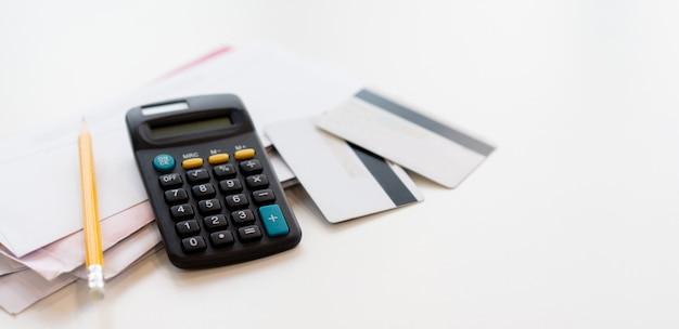 Calcolatrice con un gruppo di lettera di posta e carta di credito al tavolo per la spesa di fine mese