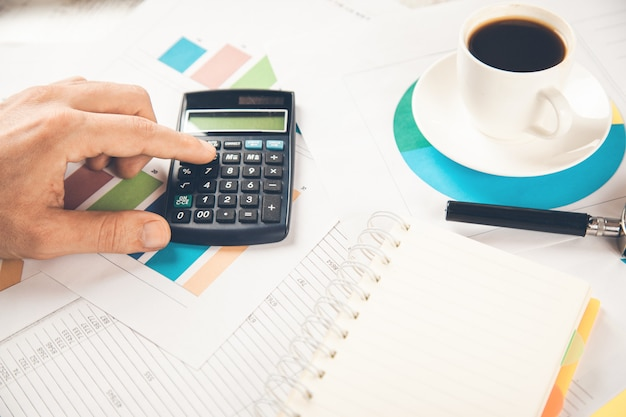Calcolatrice della mano dell'uomo sul documento con il caffè