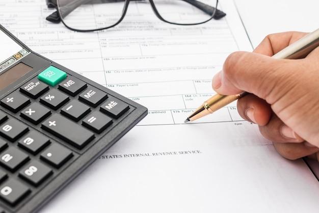 Calcolatrice e documenti per lavorare sul tavolo, finanza e risparmio, concetto di affari.