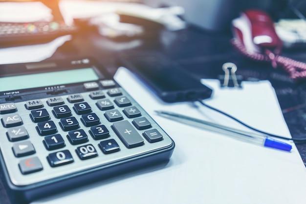 Calcolatrice e penna a sfera sul tavolo in ufficio