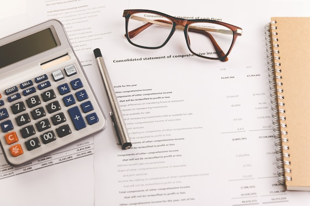 Calcolatrice, penna e bicchieri posizionati su documenti di analisi finanziaria