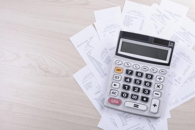 Calcolatrice per contare su una pila di assegni dagli acquisti dal negozio su un fondo di legno. vista dall'alto. posto per il testo. copia spazio