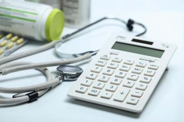 Calcolatrice, stetoscopio e bottiglie di medicina su sfondo bianco
