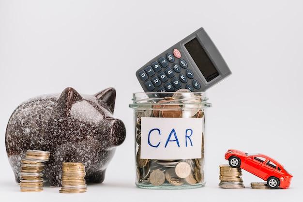 Calcolatrice sul barattolo di monete di vetro con pila di monete; auto e piggybank su sfondo bianco