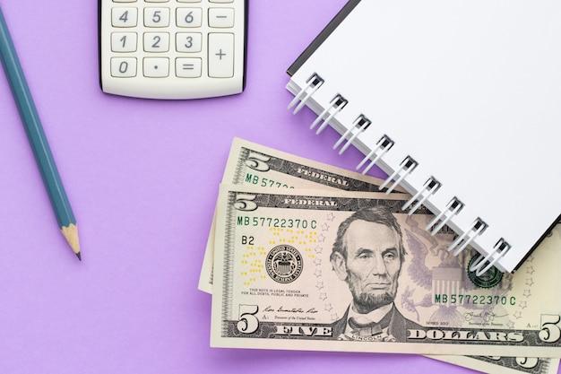 Calcolatrice, taccuino con soldi americani e una matita su un tavolo lilla
