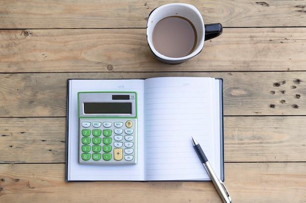 Calcolatrice, taccuino, tazza di caffè, penna su fondo di legno
