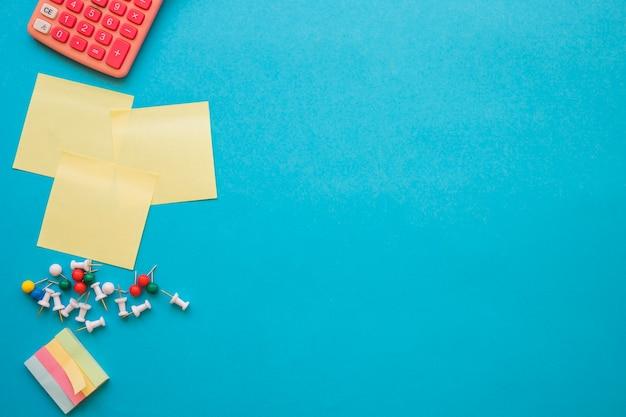 Calcolatrice vicino a perni e note adesive