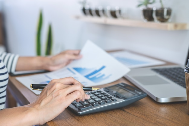 Calcoli del ragioniere femminile, controllo ed analisi dei dati finanziari del grafico con il calcolatore ed il computer portatile