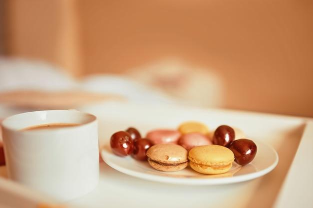 Calda tonica tazza di caffè con gustosi macarons colorati sul vassoio bianco.