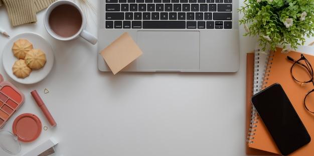 Caldo spazio di lavoro femminile beige con computer portatile, trucco e forniture per ufficio