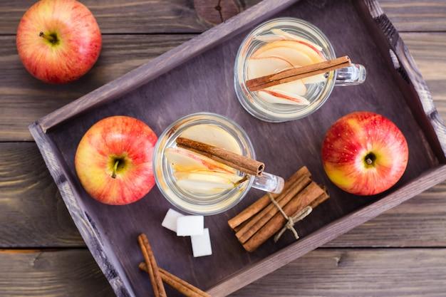 Caldo tè rilassante a base di mele e cannella in bicchieri e ingredienti per cucinare su un tavolo di legno. concetto di disintossicazione, antidepressivo. stile rustico. vista dall'alto