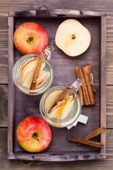 Caldo tè rilassante a base di mele e cannella in bicchieri su un tavolo di legno. concetto di disintossicazione, antidepressivo. stile rustico. vista dall'alto