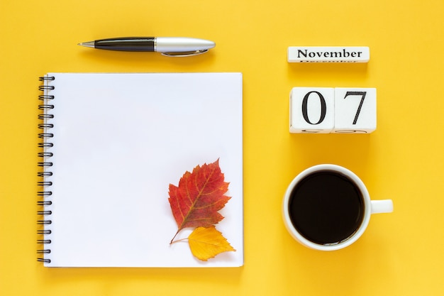 Calendario 07 novembre tazza di caffè, blocco note con penna e foglia gialla su sfondo giallo