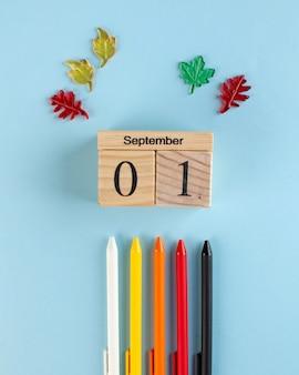 Calendario 1 settembre in legno, penne colorate su sfondo blu. inizio dell'anno scolastico