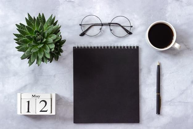 Calendario 12 maggio. blocco note nero, tazza di caffè, succulento, bicchieri su marmo