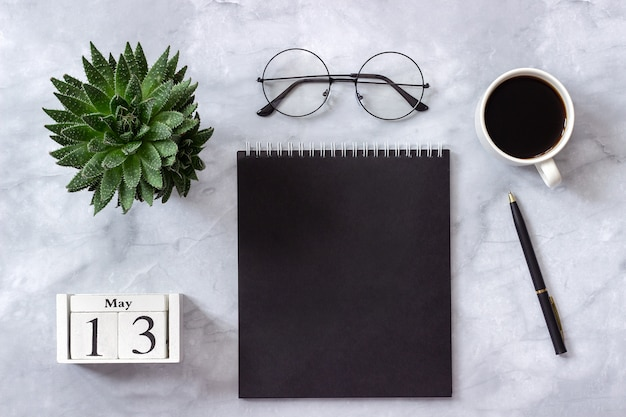 Calendario 13 maggio. blocco note nero, tazza di caffè, succulenta, bicchieri su marmo