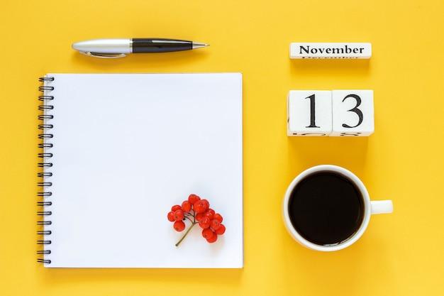 Calendario 13 novembre tazza di caffè, blocco note con penna e foglia gialla su giallo