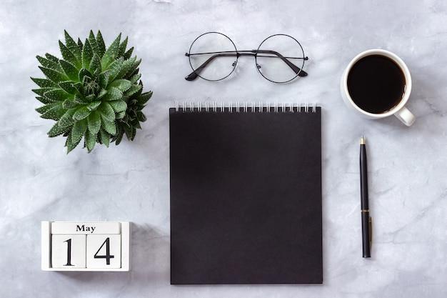 Calendario 14 maggio. blocco note nero, tazza di caffè, succulenta, bicchieri su marmo