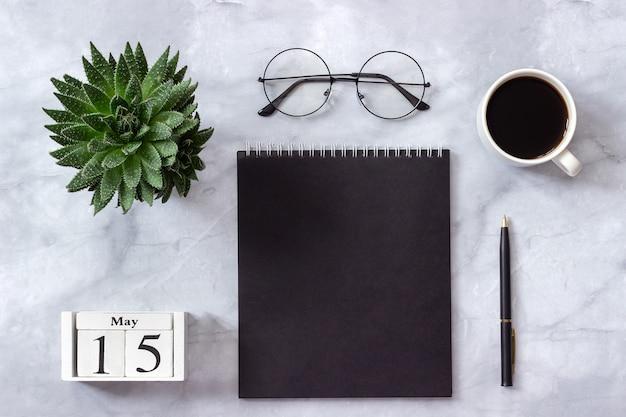 Calendario 15 maggio. blocco note nero, tazza di caffè, succulento, bicchieri su marmo