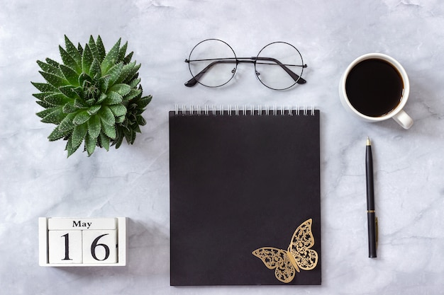 Calendario 16 maggio. blocco note nero, tazza di caffè, succulenta, bicchieri su marmo