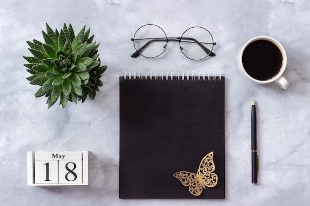 Calendario 18 maggio. blocco note nero, tazza di caffè, succulento, bicchieri su marmo