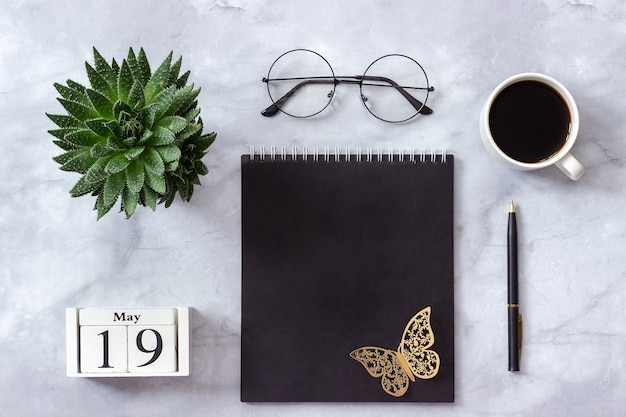 Calendario 19 maggio. blocco note nero, tazza di caffè, succulento, bicchieri in marmo
