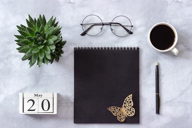 Calendario 20 maggio. blocco note nero, tazza di caffè, succulento, bicchieri su marmo