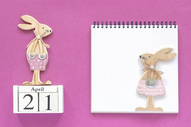 Calendario 21 aprile coniglietti pasquali, blocco note bianco su sfondo viola.