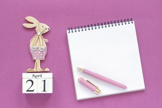 Calendario 21 aprile e coniglietto di pasqua in legno, blocco note su sfondo viola.