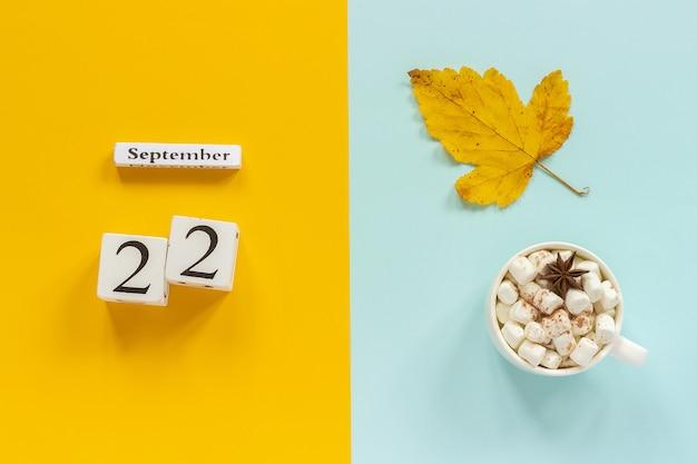 Calendario 22 settembre, tazza di cacao con marshmallow e foglie di autunno gialle su sfondo blu giallo.