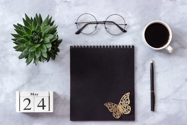 Calendario 24 maggio. blocco note nero, tazza di caffè, succulento, bicchieri su marmo
