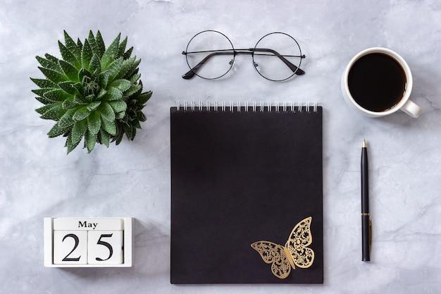 Calendario 25 maggio. blocco note nero, tazza di caffè, succulento, bicchieri su marmo