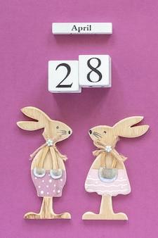 Calendario 28 aprile coniglietti di pasqua su sfondo di carta viola.