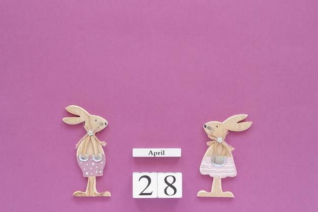 Calendario 28 aprile e coppia di coniglietti pasquali in legno su sfondo viola.
