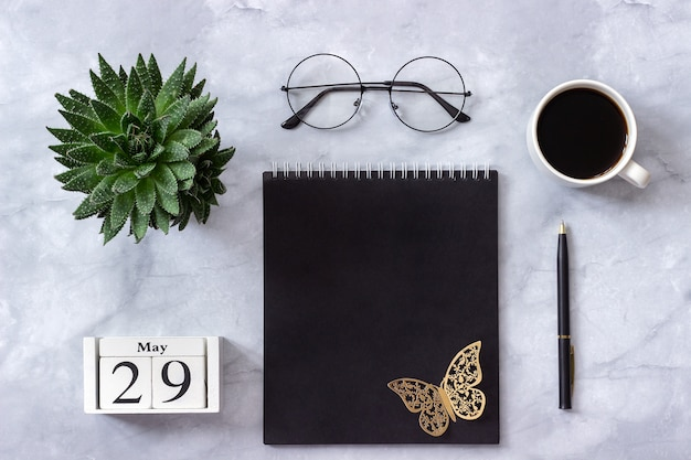 Calendario 29 maggio. blocco note nero, tazza di caffè, succulento, bicchieri in marmo