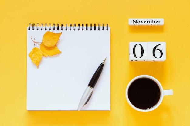 Calendario 6 novembre tazza di caffè, blocco note con penna e foglia gialla su superficie gialla