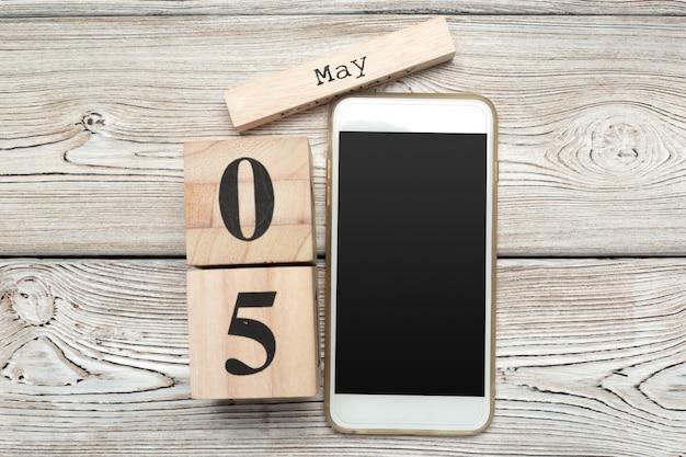 Calendario a forma di cubo di superficie in legno del 5 maggio su superficie di legno