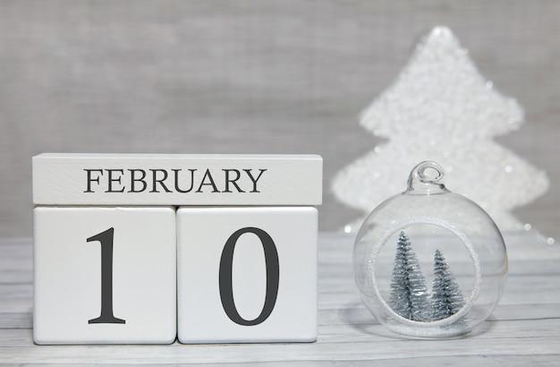 Calendario a forma di cubo per il 10 febbraio su superficie di legno e sfondo chiaro
