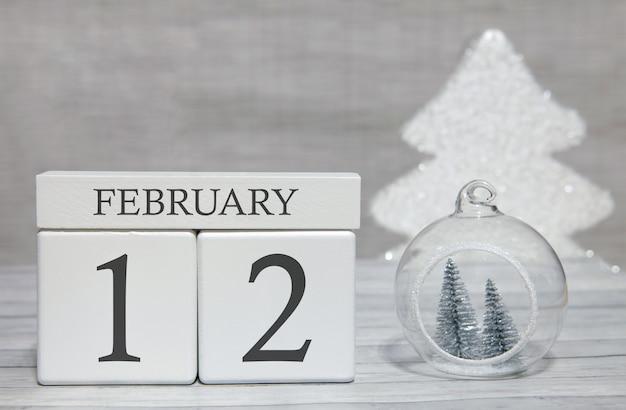 Calendario a forma di cubo per il 12 febbraio su superficie di legno e sfondo chiaro