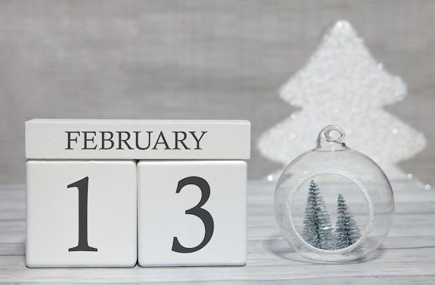 Calendario a forma di cubo per il 13 febbraio su superficie di legno e sfondo chiaro