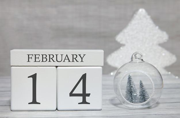 Calendario a forma di cubo per il 14 febbraio su superficie di legno e sfondo chiaro