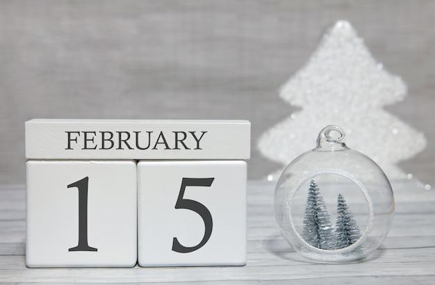 Calendario a forma di cubo per il 15 febbraio su superficie di legno e sfondo chiaro