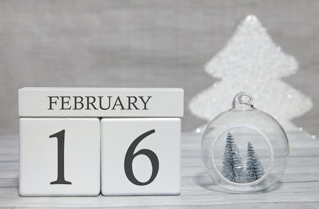 Calendario a forma di cubo per il 16 febbraio su superficie di legno e sfondo chiaro