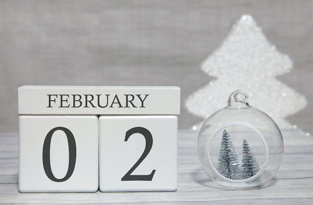 Calendario a forma di cubo per il 2 febbraio su superficie di legno e sfondo chiaro