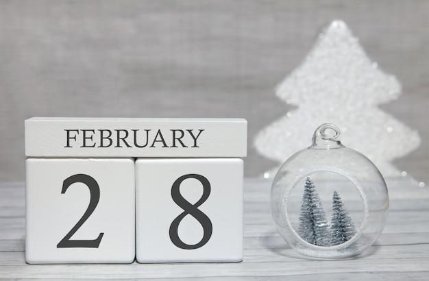 Calendario a forma di cubo per il 28 febbraio su superficie di legno e sfondo chiaro