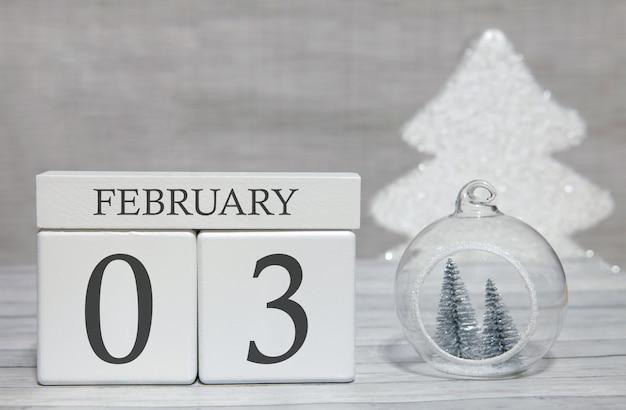 Calendario a forma di cubo per il 3 febbraio su superficie di legno e sfondo chiaro
