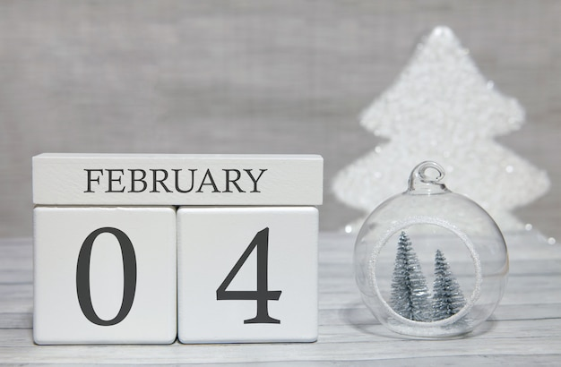Calendario a forma di cubo per il 4 febbraio su superficie di legno e sfondo chiaro