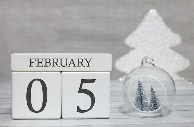 Calendario a forma di cubo per il 5 febbraio su superficie di legno e sfondo chiaro